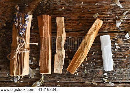 A Close Up Image Of Sacred Holy Wood Smudge Sticks With Dried Lavender And Selenite On A Dark Wooden