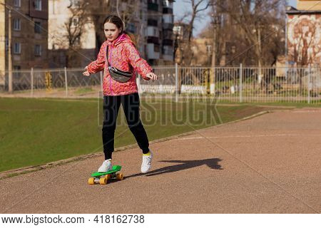 A Teenage Girl On Vacation In Bright Clothes Learns To Ride A Skateboard Or Pennyboard In The Park.