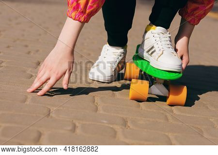 Teenage Girl Learning To Ride A Green Skateboard Or Pennyboard. Active Teenager Quickly Rides A Skat