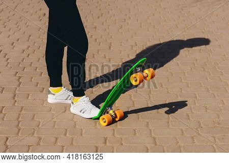 The Girl Is Rolling On The Penny Board. The Child Is Dressed In Bright Clothes And Is Learning To Ri