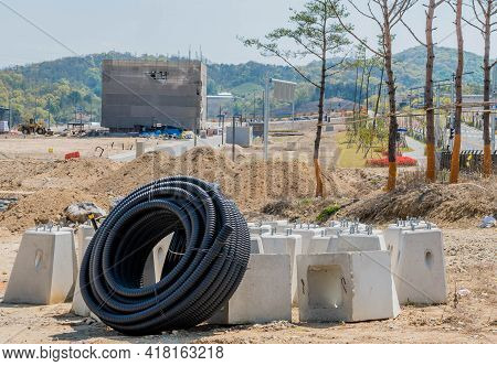 Daejeon, South Korea; April 18, 2021: Large Roll Of Flexible Pvc Pipe Leaning Against Concrete Lampp