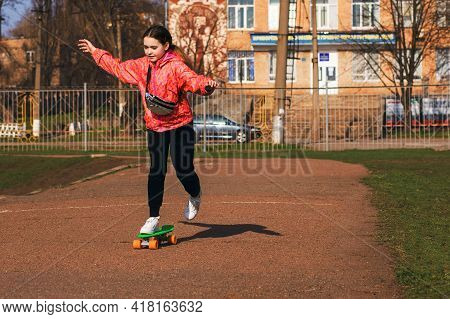 Teenage Girl On Vacation In Bright Clothes Ride A Skateboard Or Pennyboard In The Park. Skateboardin