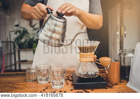 Person Holding Kettle Pour Hot Water Over The Coffee Powder. Making Filter Coffee. Drip Coffee.