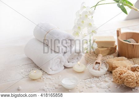Spa bath setting with green leaves , orchid,bottles of essential oil  , herbal ball, salt in bowl ,candle , herbal ,ball on wooden background