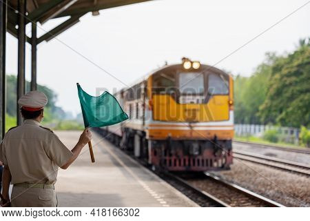 Selective Focused, Green Flag Raised Up By Officer For Safety Symbol To Driver Driving Depart Railwa
