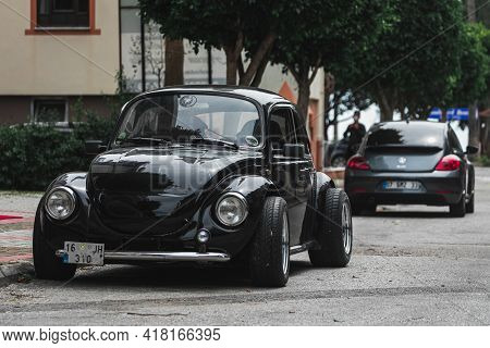 Alanya, Turkey - April 12 2021:   Two Vintage Black Volkswagen Beetle Cars Of Different Generations