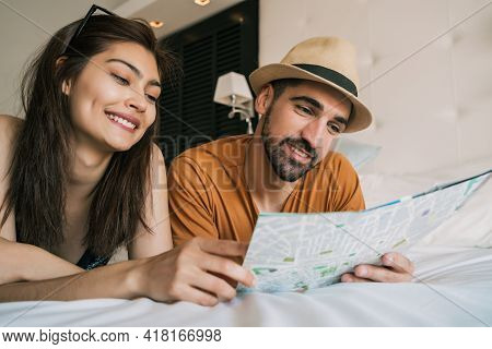 Couple Organizing Their Trip At Hotel Room.