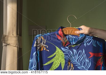Housewife's Hand Raising Her Husband's Hawaiian Shirt On Hanger To Check For Tidy And Cleanliness On