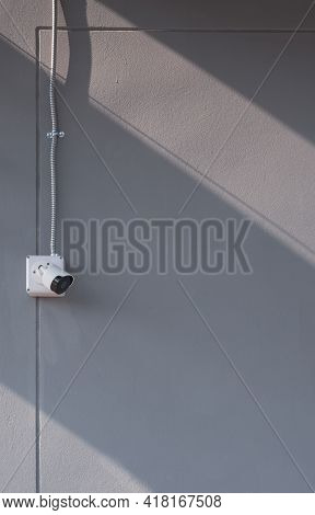 Sunlight And Shadow On Surface Of Security Camera With Flexible Metal Conduit On Gray Cement Wall In