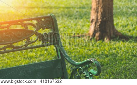 Morning Sunlight On Backrest Surface Of The Old Empty Metal Park Bench On Green Lawn In Public Park