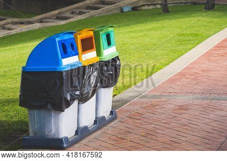 Perspective Side View Of 3 Colorful Garbage Bins For Separate Waste Sorting On Stone Tiles Pavement