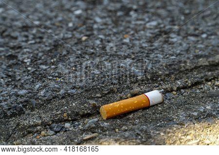 Cigarette Stub Of White On Black Cement
