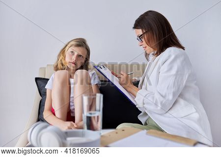 Girl Child At Session With Female Psychologist Counselor Social Worker In Office