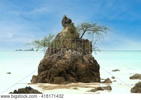 Rocky Beach With A View Of Rock And Sea. Rocky Cliffs And Sea Waves On Sandy Beach.