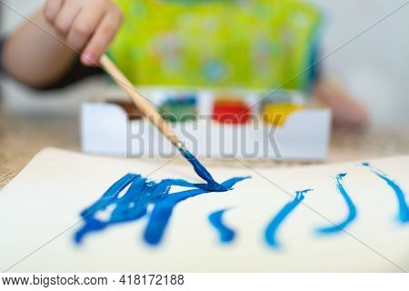 Top View Of The Small Child Is Drawing With Bright Paints On Paper With Soft Effect, Close Up.
