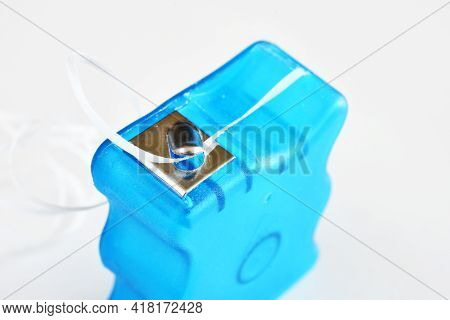 A Close Up Image Of A Blue Dental Floss Container On A White Background.