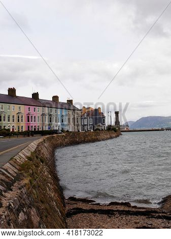Vertical Shot Of Caernarvon Seafront With Row Of Colourful Houses. High Quality Photo
