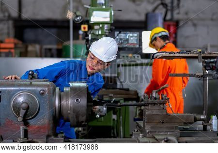 Asian Factory Worker Woman Look To Part Of The Machine And Inspect The Function While Her Co-worker