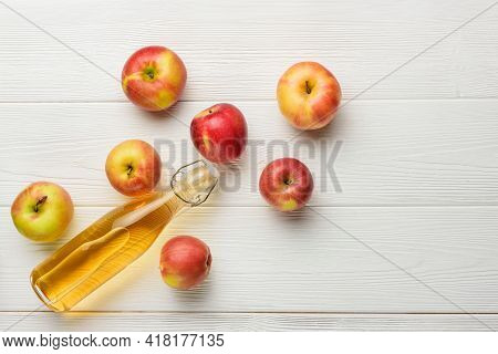 A Bottle Of Apple Juice And A Few Apples On The Background Of White Boards With Copy Space. Flat Lay