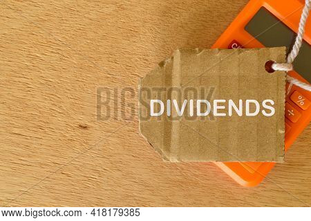 Phrase Dividends Written On Cork Board With Calculator.