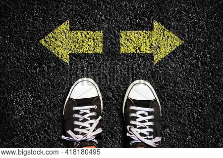 Sneakers On An Asphalt Road. Yellow Arrows Pointing In Different Directions. View From Above. The Co