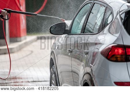 Woman Washing Car With Pressure Washer At Self-service Car Wash Station, Selective Focus