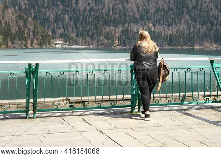The Lone Figure Of A Fair-haired, Voluptuous Woman Standing By A Fence On The Steep Shore Of A Mount