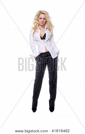 Full Length Portrait Of A Stylish Young Woman In Men Style Standing With Hands In Pockets Over White