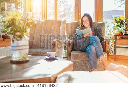 Cheerful Smiling Female Dressed Cozy Home Clothes Sitting In Comfortable Armchair, Relaxing, Reading