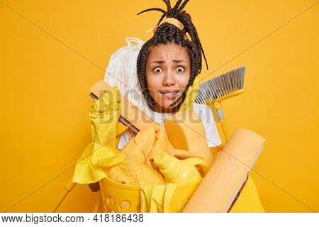 Puzzled Worried Young Afro American Woman Overwhelmed With Cleaning Surrounded By Different Tools Na