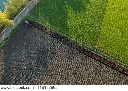 Aerial View With A Drone Of A Farmer With Tractor Plowing A Spring Wavy Agricultural Countryside Lan