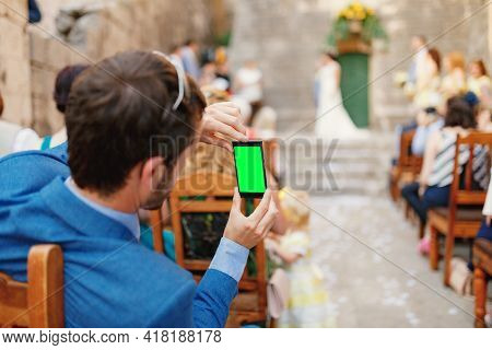 Man Photographs A Wedding Ceremony On A Smartphone. Blank Screen