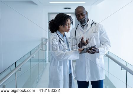 Diverse male and female doctor talking seriously and looking at digital tablet in hospital corridor. medicine, health and healthcare services.
