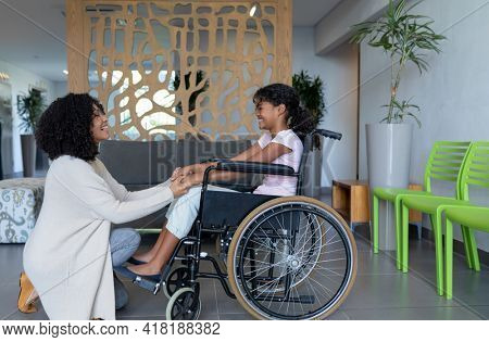 Happy mixed race mother kneeling holding hands with smiling daughter in wheelchair in hospital foyer. medicine, health and healthcare services.