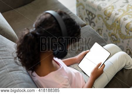Elevated view of mixed race girl wearing wireless headphones sitting on couch using digital tablet. teenage lifestyle, leisure time, communication and technology.