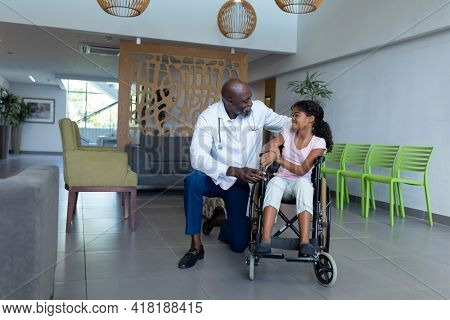 African american male doctor kneeling to talk with mixed race girl in wheelchair in hospital foyer. medicine, health and healthcare services.