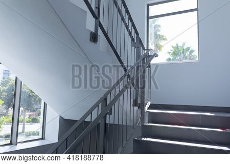 Stairs lit by daylight from windows on landing of staircase in mid 20th century building. architecture and practical interior design.
