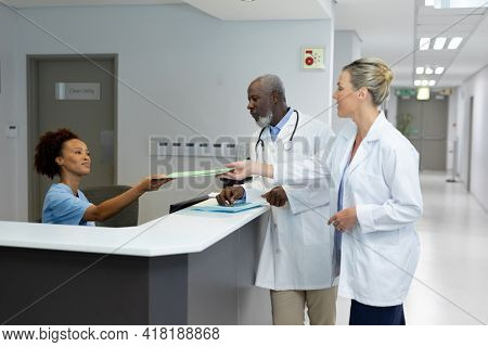 African american receptionist passing document to caucasian female doctor at hospital reception. medicine, health and healthcare services.