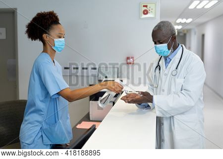 Diverse male and female doctors wearing face masks disinfecting hands over the counter at hospital. medicine, health and healthcare services during coronavirus covid 19 pandemic.