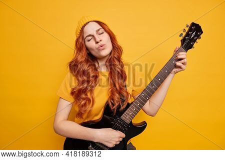 Pleased Relaxed Female Guitarist Plays Bass Guitar Closes Eyes From Satisfaction Sings Song Has Red