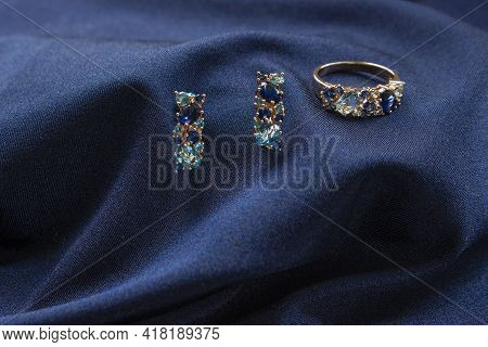 Pair Of Platinum Earring With Sapphire Gemstone On Blue Satin Background. Luxury Female Jewelry, Clo