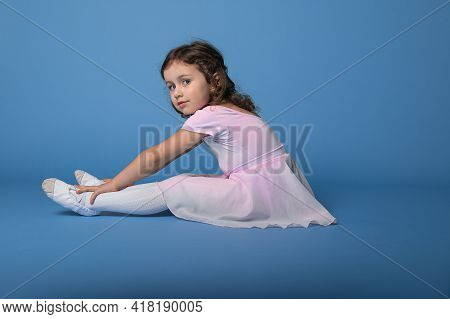 Side Portrait Of A Little Ballerina Performing Stretching Legs, Sitting Over Blue Background With Sp