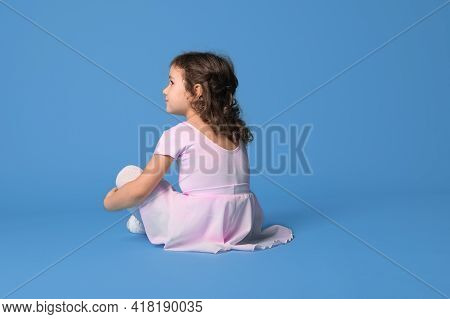 View From The Back Of A Girl Ballerina Dressed In Pink Uniform Looking Away Sitting On A Blue Backgr