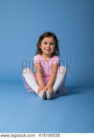Portrait On A Blue Background Of A Cute Ballerina In A Pink Dress Stretching Her Body. Copy Space