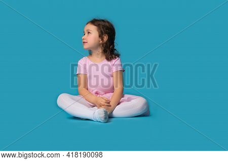 Isolated Portrait Of Adorable Girl, Ballerina, Sitting And Looking To The Side On Blue Background Wi