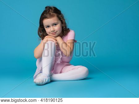 Adorable Preschool Girl Child, Ballet Dancer, Posing To The Camera, Sitting Over Blue Background Wit