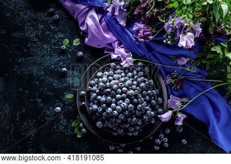 Fresh Juicy Blueberries On A Black Plate. Summer Still Life With Blueberries, Colored Sweet Peas And