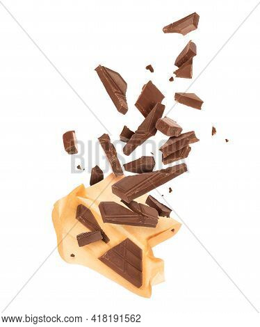 Pieces Of Crushed Chocolate Are Fly Out From A Paper Wrapper, Isolated On A White Background