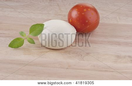 mozzarella on chopping board with tomato and basil