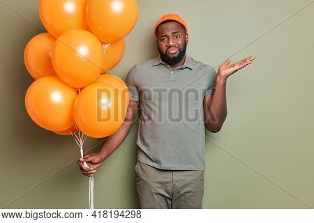 Photo Of Confused Puzzled Birthday Guy With Dark Skin And Thick Beard Raises Palm Up Looks Hesitant